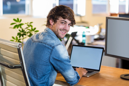 attractive office: Smiling casual businessman sitting at desk in the office