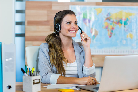 headset woman: Pretty travel agent speaking to customer in the office