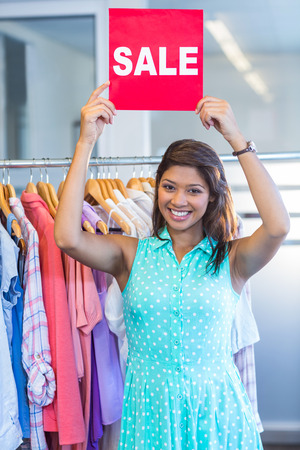 rood teken: Beautiful brunette holding red sign in clothes store