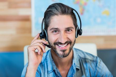 servicio al cliente: Sonriendo agente de viajes que mira la c�mara en la oficina