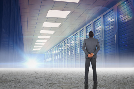 hands behind back: Young businessman standing with hands behind back against server hallway in desert setting