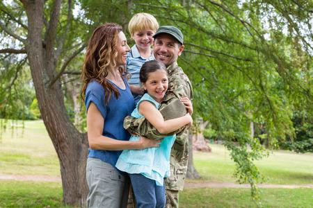 embrace family: Apuesto soldado reunirse con la familia en un día soleado