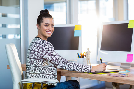 digitizer: Beautiful brunette sitting at her desk and working with digitizer in the office Stock Photo