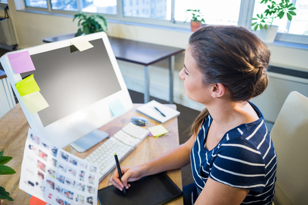 digitizer: Smiling brunette working with photographs and digitizer in the office