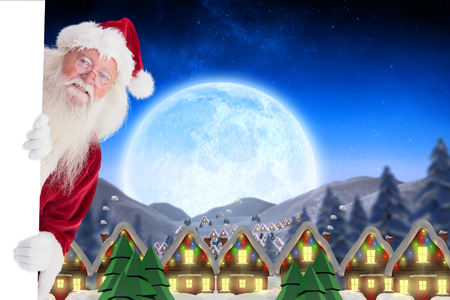 out of town: Santa looks out behind a wall against quaint town with bright moon