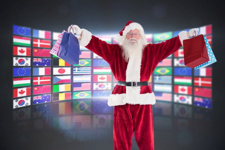international flags: Santa holds some bags for Chistmas against screen collage showing international flags