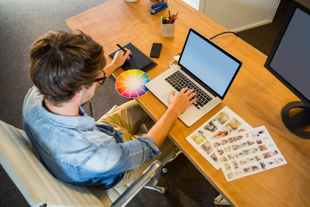 graphic designers: Designer working with colour wheel and digitizer in the office