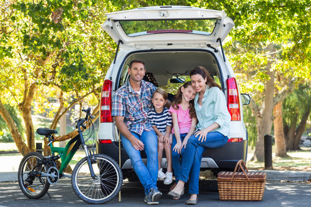 HAPPY FAMILY: Familia feliz que consigue listo para viaje por carretera en un d�a soleado Foto de archivo