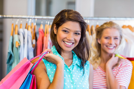 choosing clothes: Smiling friends holding shopping bags in clothes store