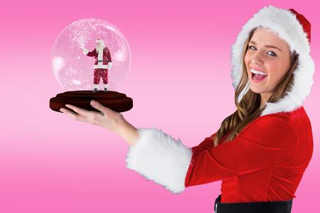 pere noel sexy: Image composite de p�re no�l sexy girl holding globe de neige contre le rose
