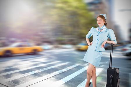 hotesse avion: Jolie h�tesse de l'air se penchant sur valise contre les nouveaux rue York