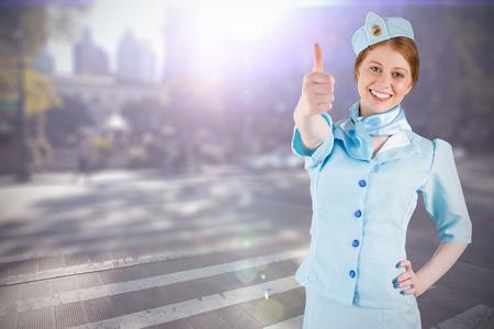 hotesse de l air: Pretty air hostess with hand on hip against blurred new york street