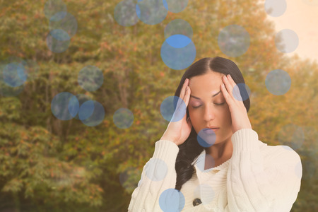 Woman suffering from a migraine against peaceful autumn scene in forest