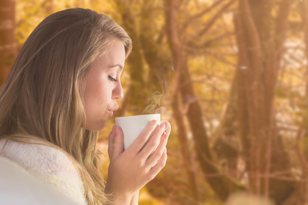 tranquil: Pretty blonde relaxing on the couch with tea against tranquil autumn scene in forest Stock Photo