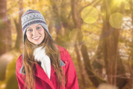 warm clothing: Pretty redhead in warm clothing against tranquil autumn scene in forest
