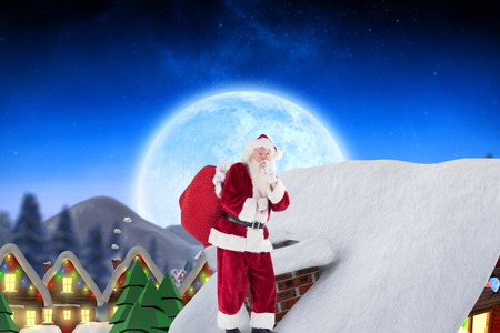 quaint: Santa on cottage roof  against quaint town with bright moon