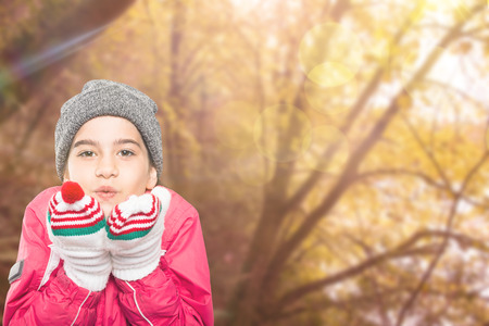 wrapped up: Wrapped up little girl blowing over hands against tranquil autumn scene in forest