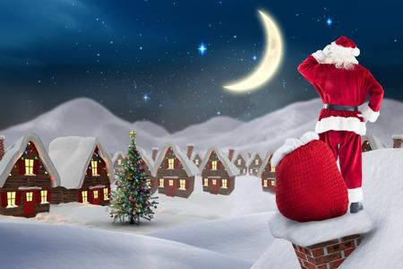 santas village: Santa on cottage roof  against cute christmas village at night Stock Photo