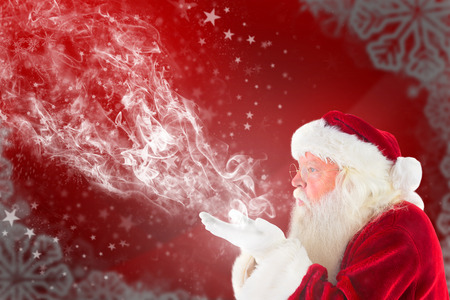 blows: Santa Claus blows something away against blurred christmas frame Stock Photo