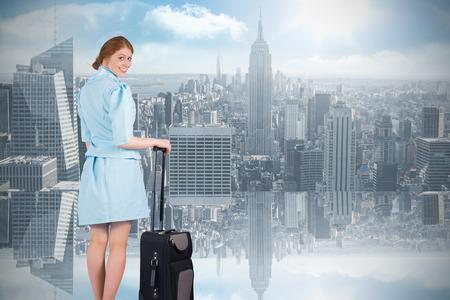 hotesse avion: Jolie h�tesse de l'air se penchant sur valise contre chambre avec grande fen�tre donnant sur la ville Banque d'images