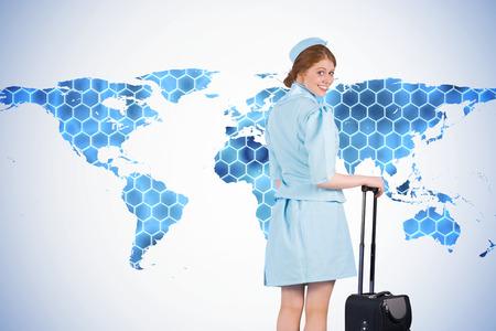 hotesse de l air: Jolie h�tesse de l'air se penchant sur la valise sur le fond avec des hexagones et carte du monde