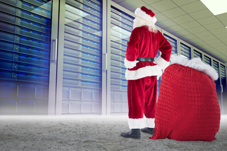 network server: Happy santa with sack of gifts against server towers in desert setting