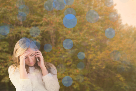 phoning: Pretty blonde getting a headache against peaceful autumn scene in forest Stock Photo