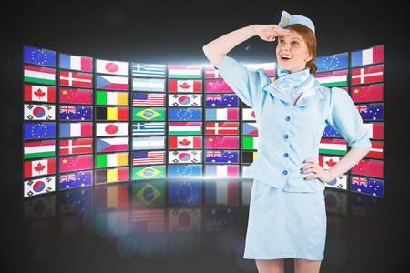 hotesse avion: Jolie h�tesse de l'air � la recherche contre le collage d'�cran montrant des drapeaux internationaux Banque d'images