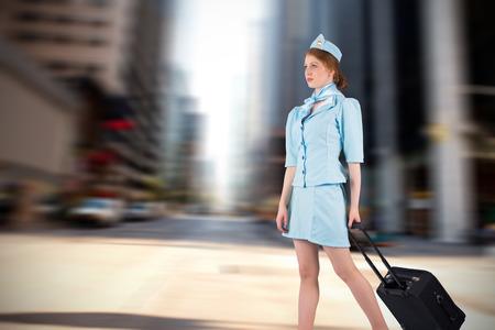 hotesse avion: Jolie h�tesse de l'air en tirant valise contre les nouveaux rue York Banque d'images
