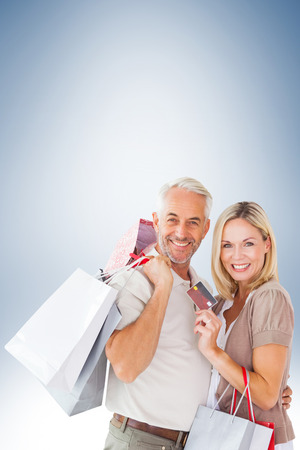 man holding card: Happy couple with shopping bags and credit card against blue vignette