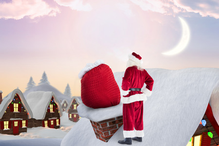 santas village: Santa on cottage roof  against cute christmas village with tree