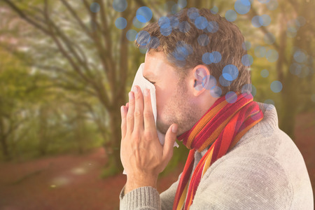 blowing nose: Man blowing nose on tissue against peaceful autumn scene in forest