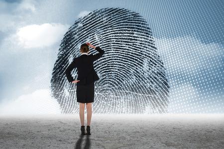 odcisk kciuka: Młoda businesswoman stały i myślenia z grafiką odcisku palca na pustyni
