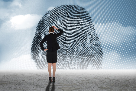 odcisk kciuka: Young businesswoman standing and thinking against thumbprint graphic over desert Zdjęcie Seryjne