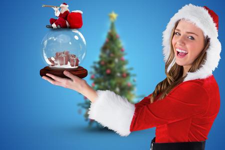pere noel sexy: Image composite de p�re no�l sexy fille tenant un globe de neige contre l'arbre de No�l floue Banque d'images
