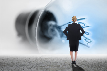 filament: Businesswoman standing with hands on hips against idea filament in light bulb Stock Photo