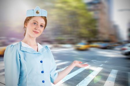 hotesse avion: H�tesse de l'air Jolie pr�sentant avec la main contre la nouvelle rue york