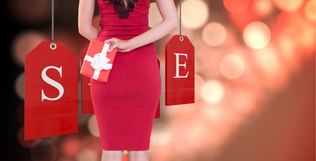 gift behind back: Classy woman holding a gift against light circles on black background Stock Photo