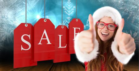 consumerism: Festive redhead smiling at camera against shimmering light design over boards
