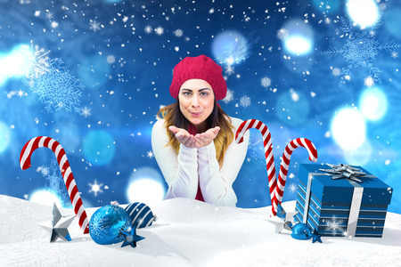 merry time: Brunette in winter clothes with hands out against christmas scene with gifts and candy canes Stock Photo