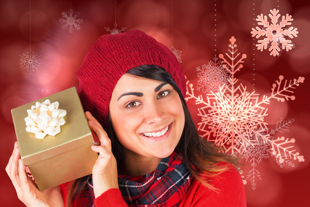 guessing: Pretty brunette in hat holding a gift  against red snow flake pattern design
