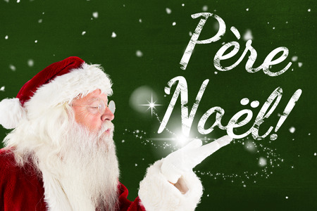 pere noel: Santa claus blowing christmas massage against green