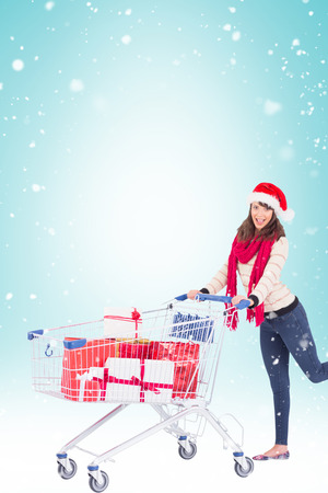 shopping trolley: Cute woman in santa hat with shopping trolley against blue vignette