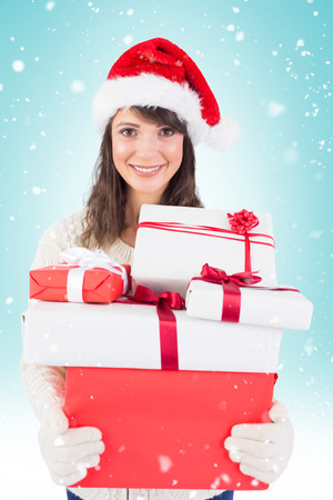wearing santa hat: Attractive woman wearing santa hat with gifts against blue vignette