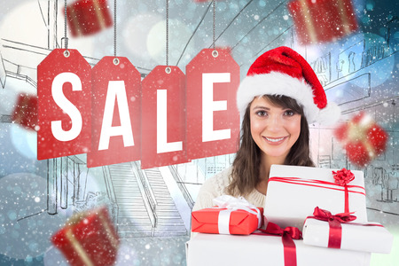 wearing santa hat: Attractive woman wearing santa hat with gifts against light glowing dots on blue
