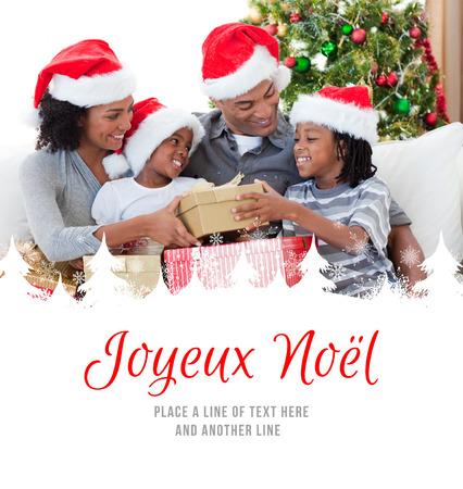 joyeux: Family holding Christmas gifts against joyeux noel