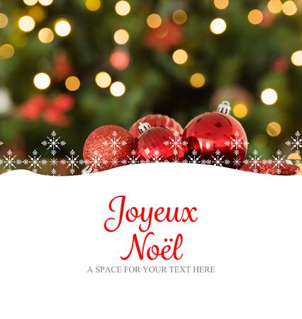 joyeux: Joyeux noel against focus on red christmas baubles