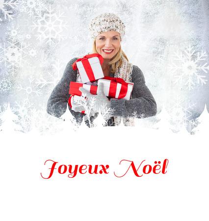 joyeux: happy blonde with gifts against joyeux noel
