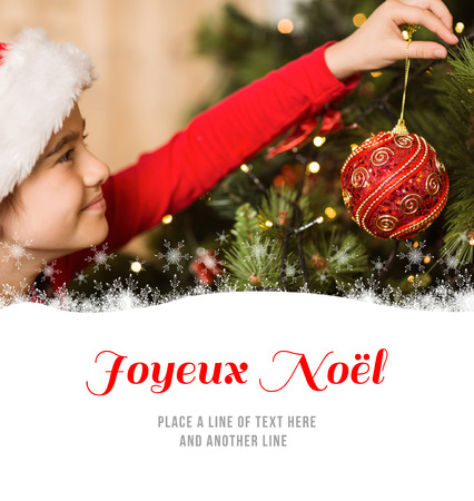 joyeux: Festive little girl hanging a christmas decoration against joyeux noel Stock Photo