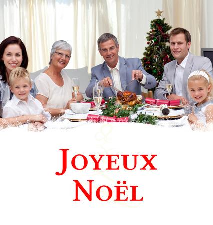Family eating turkey in Christmas Eve Dinner against tree spiral